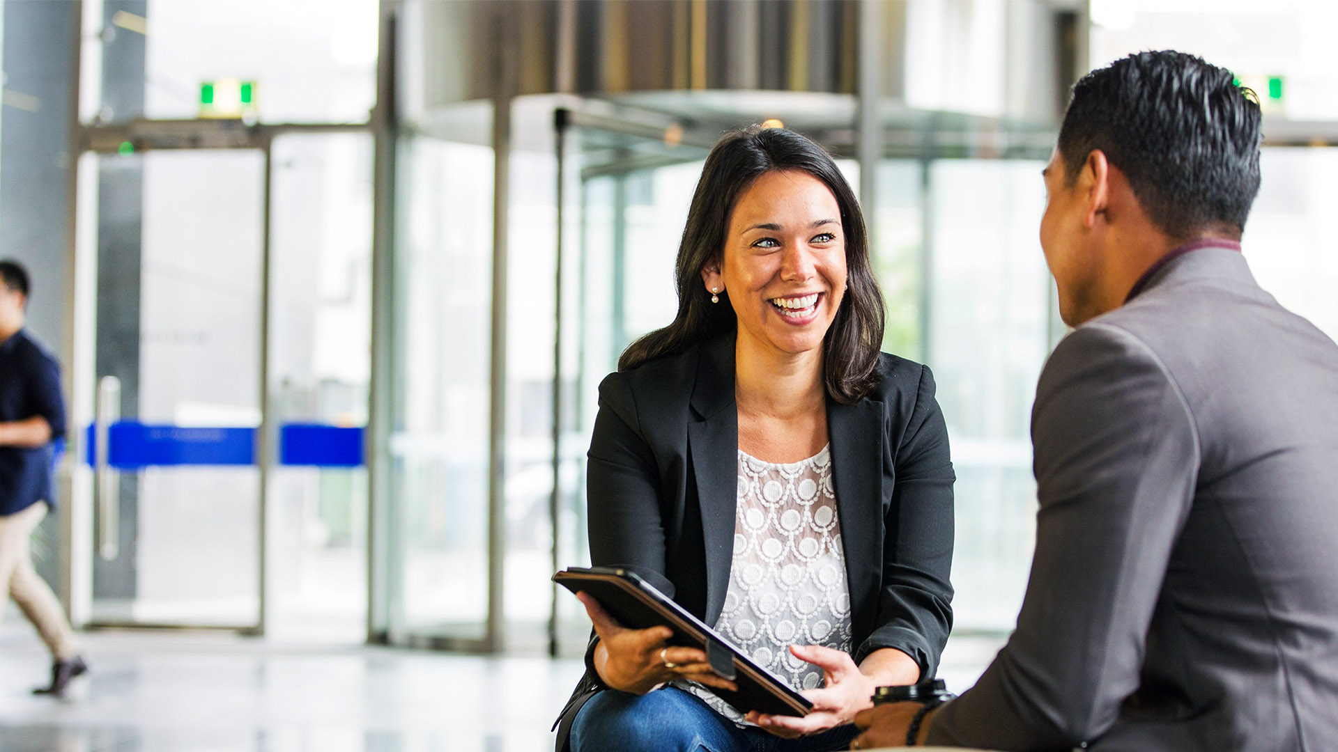 A business woman and man talking in a building lobby.