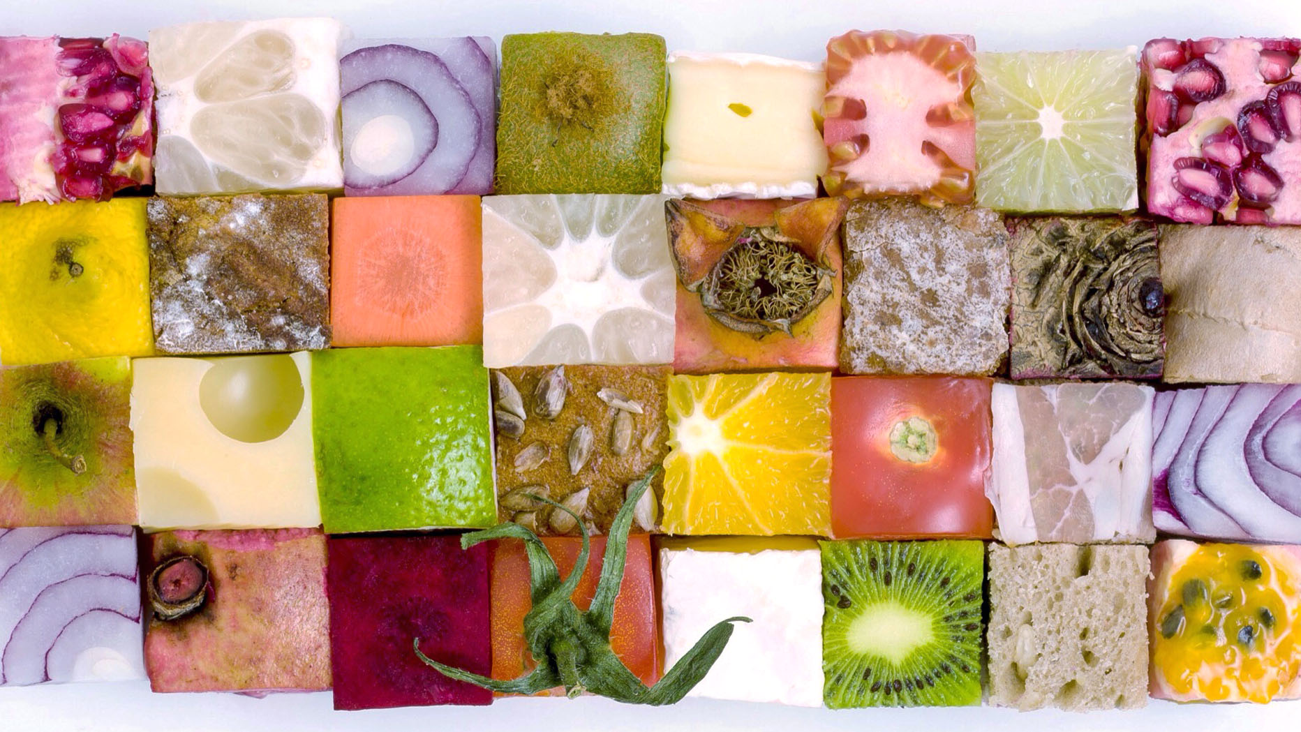 pieces of cheese, fruit and vegetables cut into squares and arranged in a checkerboard pattern