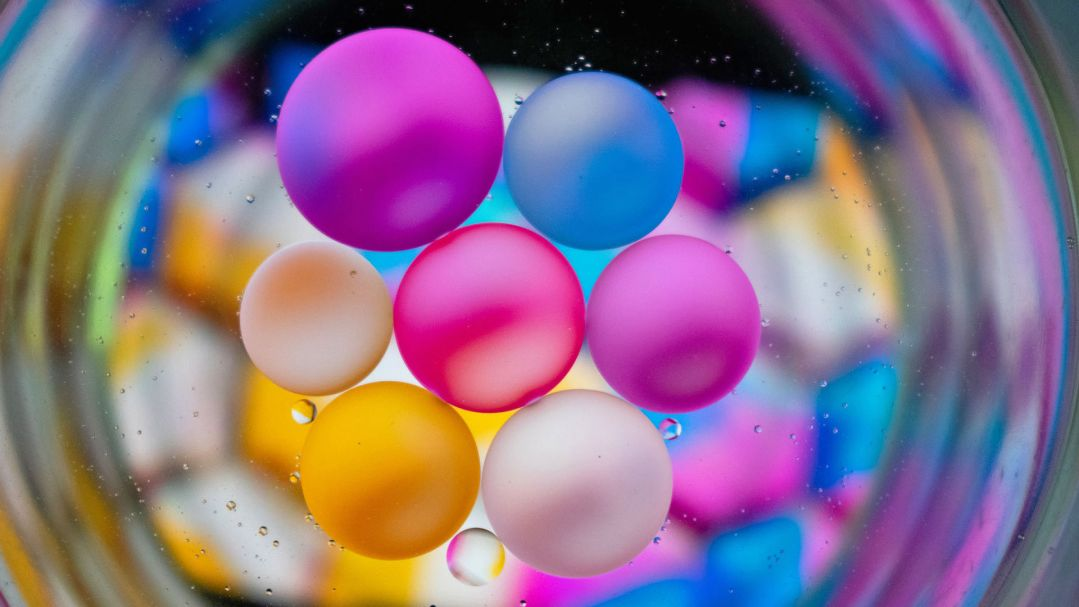 Beads of pink, blue, yellow and pearl oil floating in a shallow water dish, seen from below