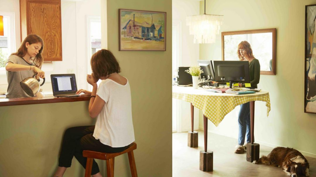 Three women at home. One is pouring a cup of tea in the kitchen, another is at her laptop at the kitchen nook, the other is standing at the dining room table using a home office set up