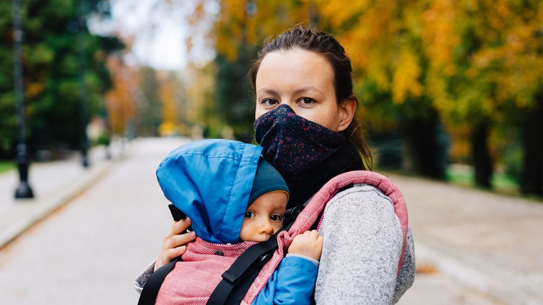 A woman in a park, she is wearing a black face mask and holding a baby