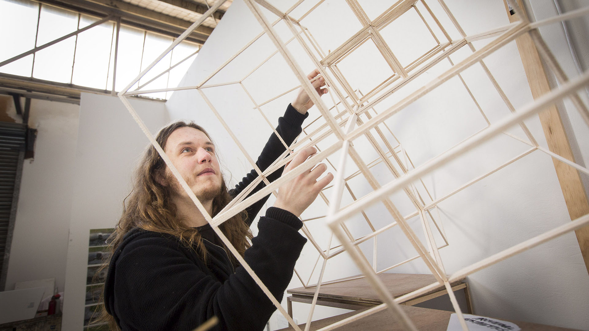 A design student with a 3D model made from dowel