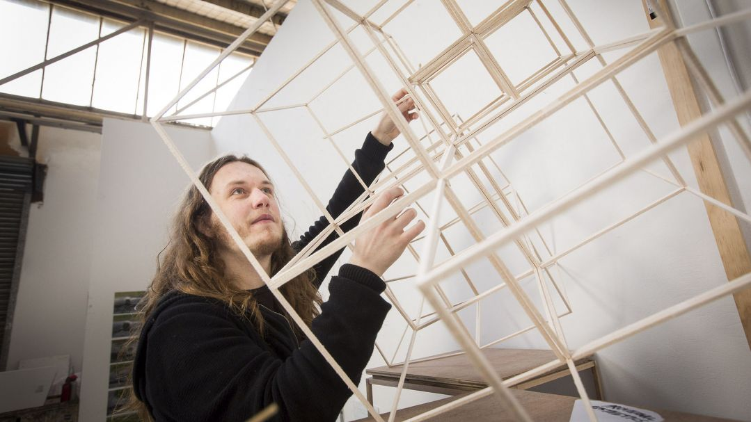 A person with long hair and a black jumper, holding a large 3D model made from wood