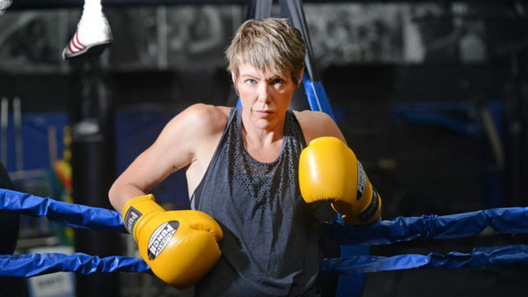 A woman wearing yellow boxing gloves leaning against a blue boxing ring