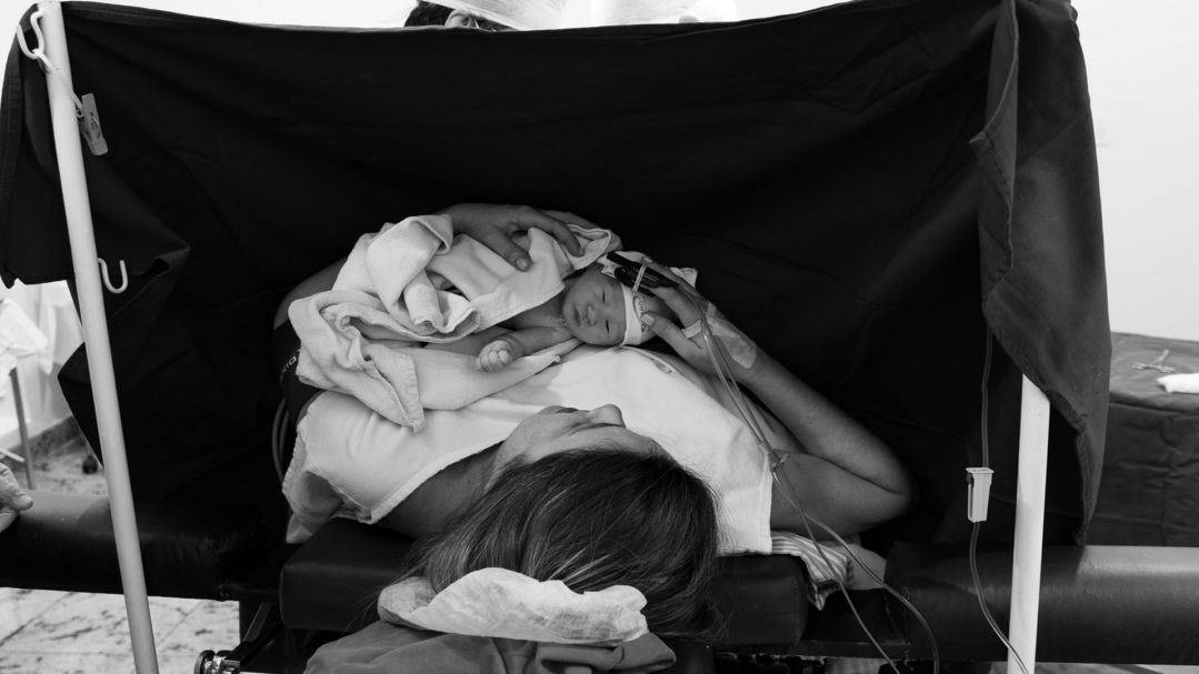 black and white image of a woman holding her baby after a Caesarean