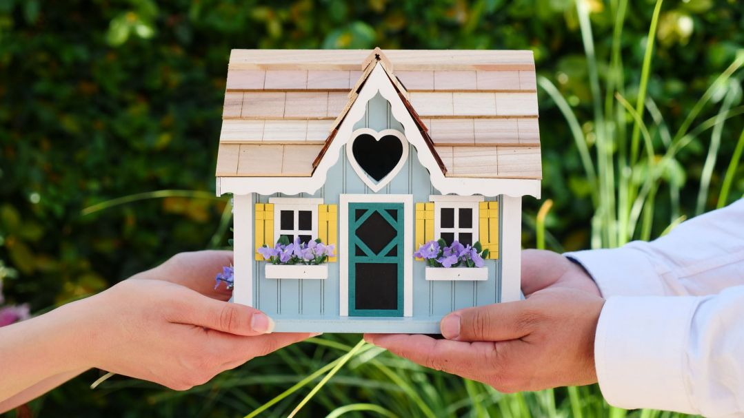 Two people holding up a model of a cute family home