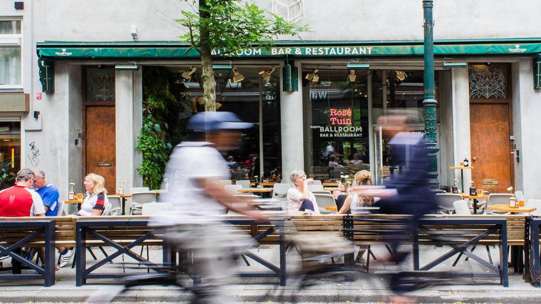 People sitting at a cafe with a person on bicycle blurred in foreground