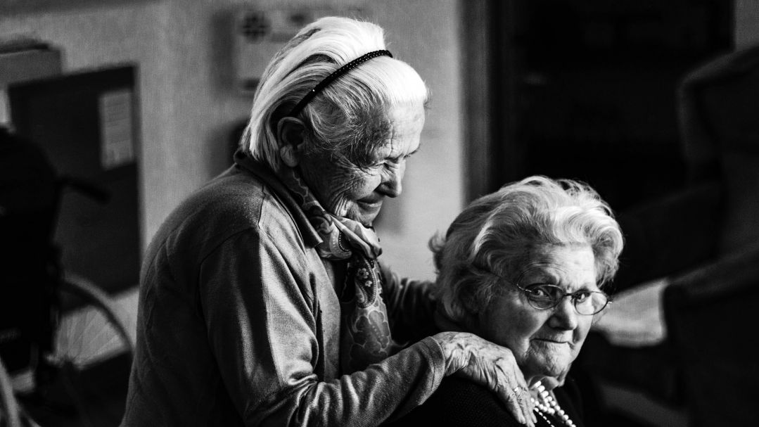 Black and white image of two older women. one is sitting the other stands behind her with her hands on her shoulder.