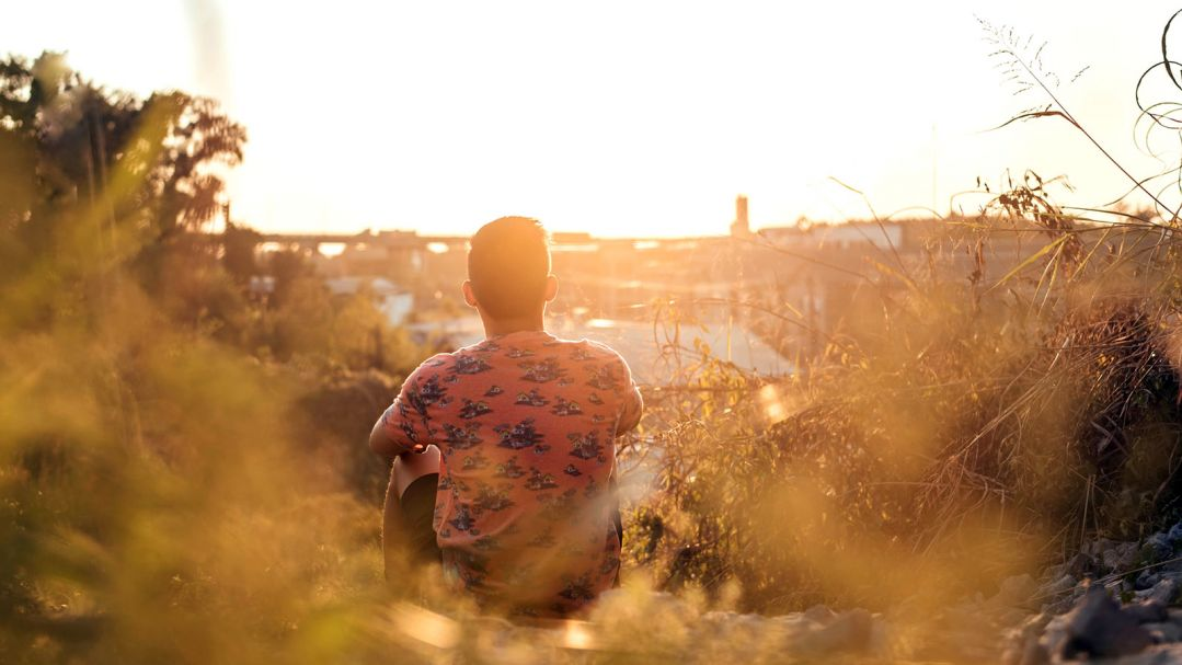 A man sitting facing a riverscape in the sunset