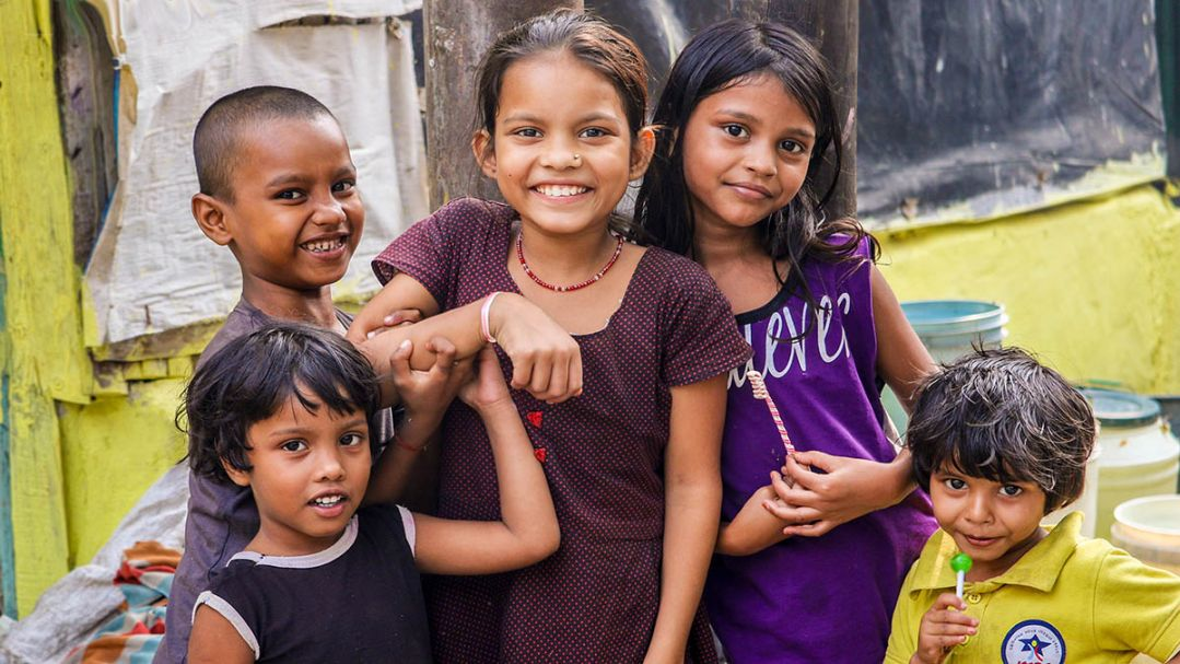 Five smiling children on a street in India