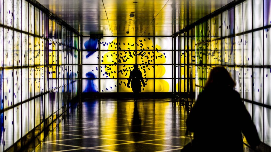 Two people walking in a hallway with brightly lit digital screen