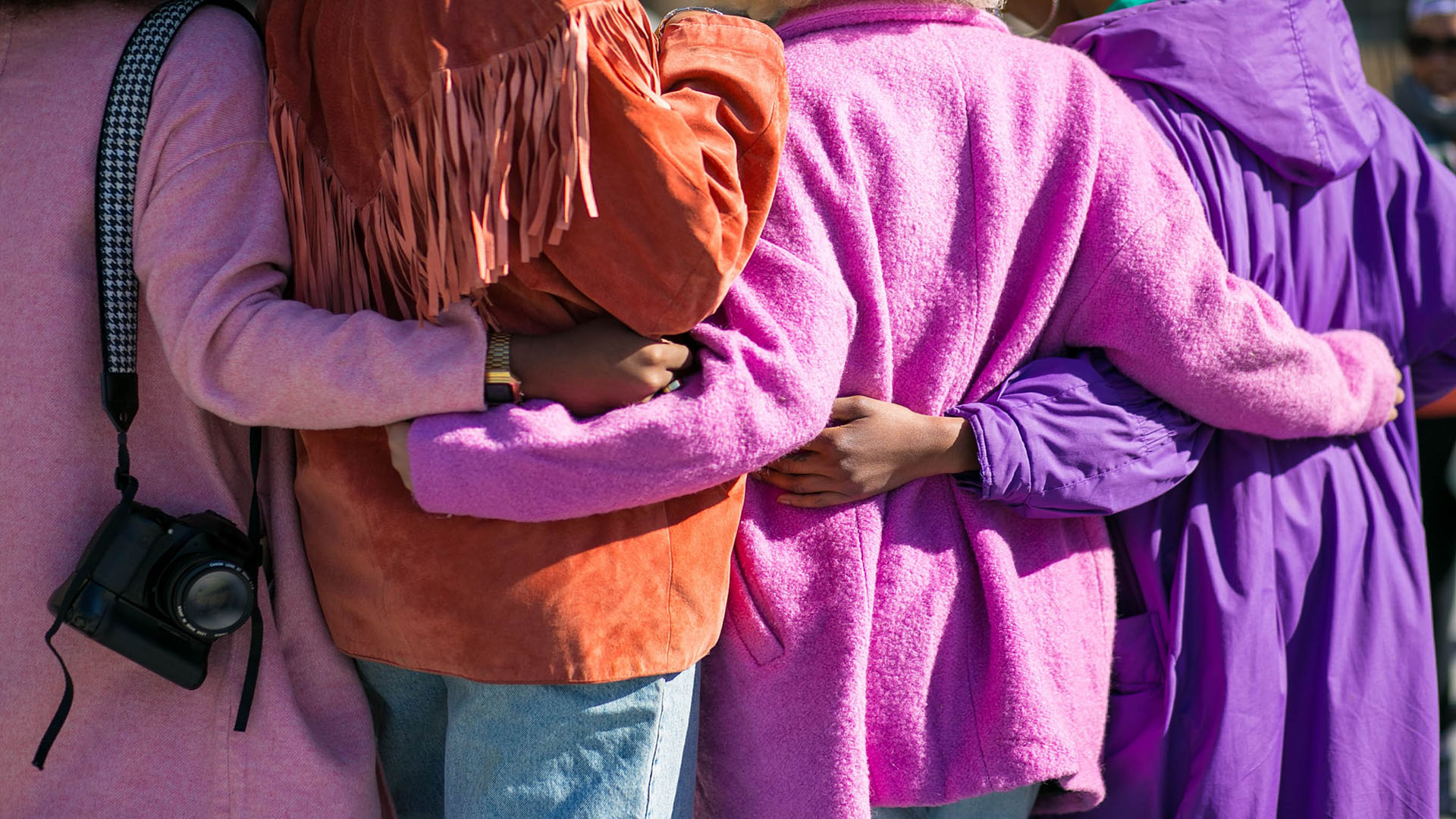Four women facing away from the camera, their arms are linked behind their backs. They are wearing purple, red and pink coats.