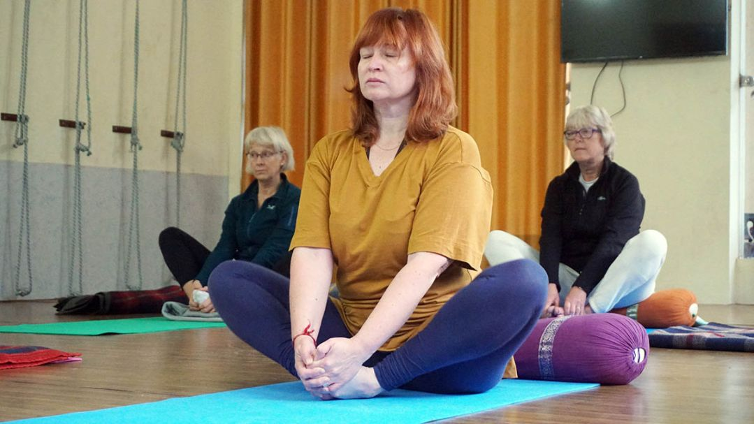 An older woman in a yoga class doing a seated stretch. She is wearing a gold t-shirt and blue leggings.