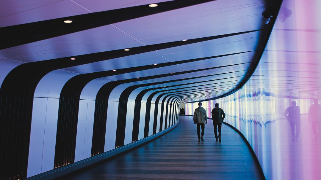 Two people walking along a curved hallway, that is lit in a purple glow