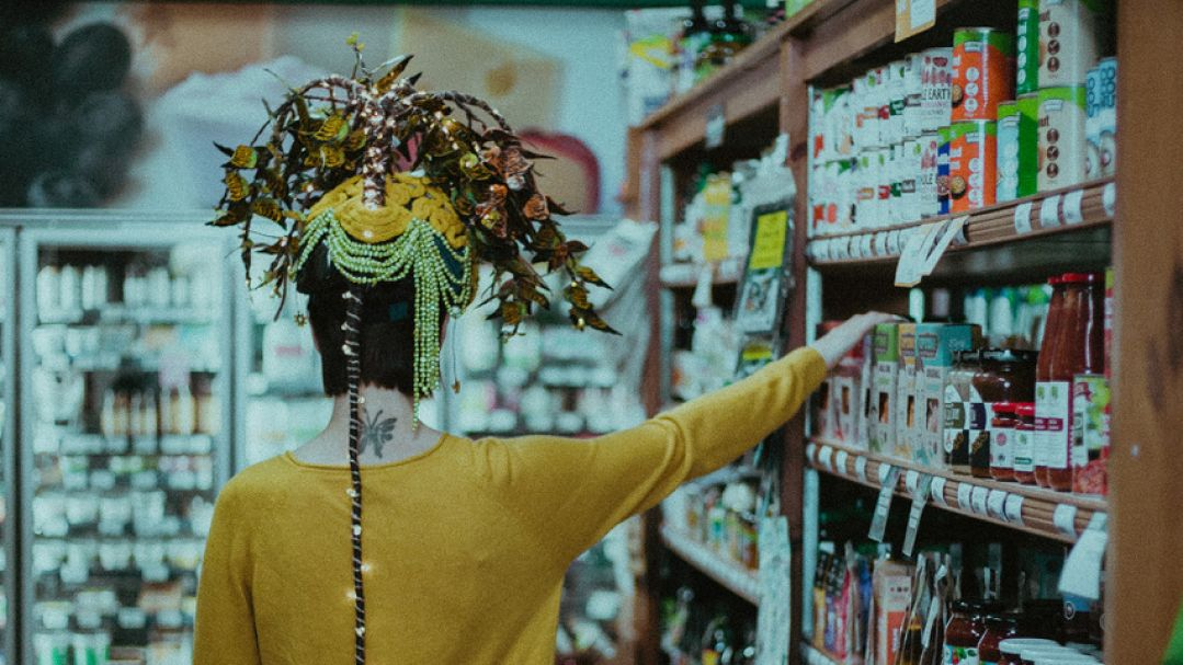 A woman with a crown-like headdreass taking an item off a supermarket shelf