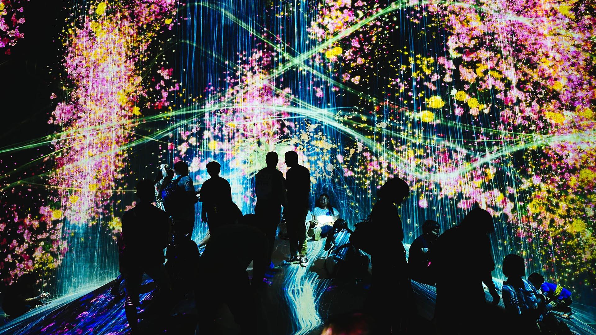 People  at a museum walking in front of a projection of a waterfall and neon colours