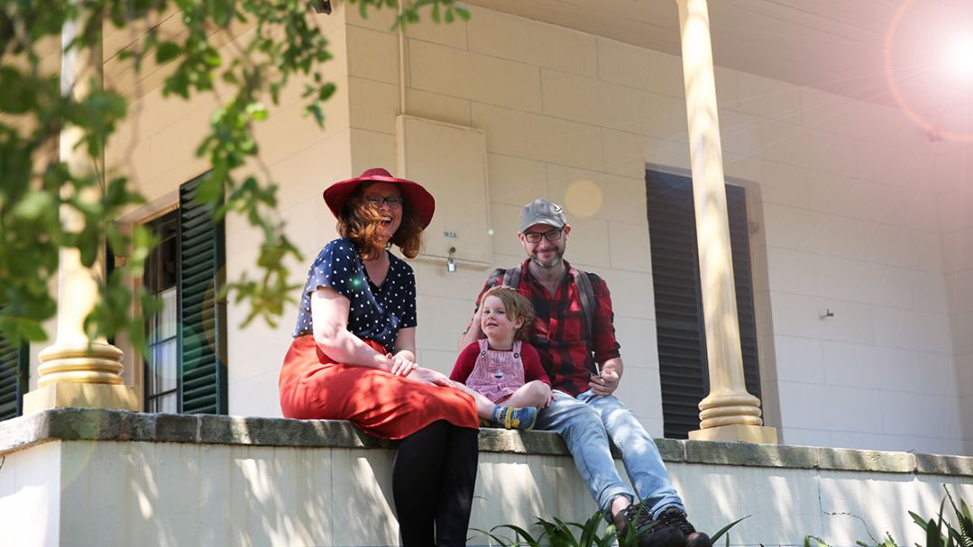 A woman in a red hat, a man in a check shirt and a toddler sitting on the verandah of a colonial era house