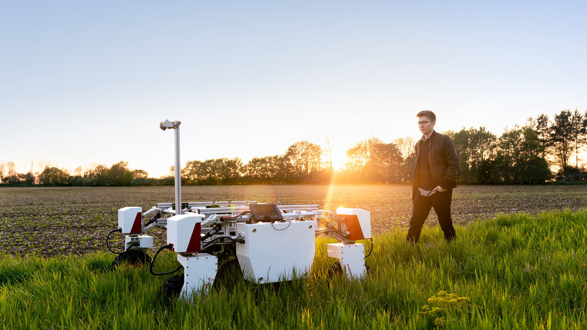 A person standing in a lush green field next to new farming equipment. the sun it setting behind them