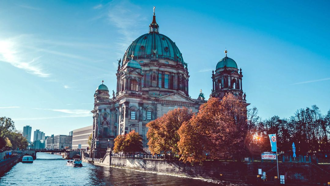 An old domed cathedral sitting alongside a river