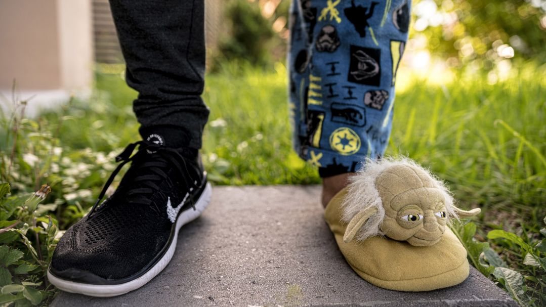 A person standing outside wearing dark jeans and black sneaker on one leg and pajama pants and a Yoda-shaped slipper on their other leg