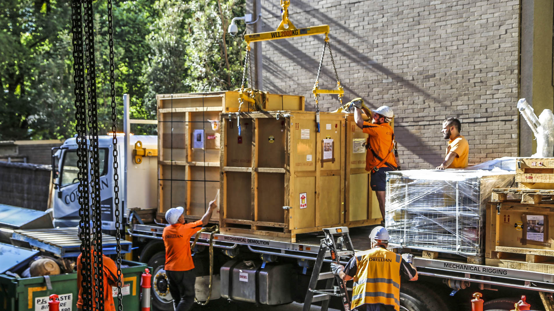 People helping affix a large box to a crane