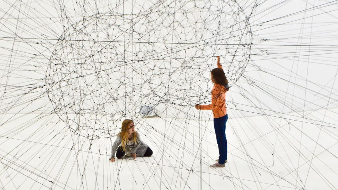Two children playing in an elaborate string-based installation artwork