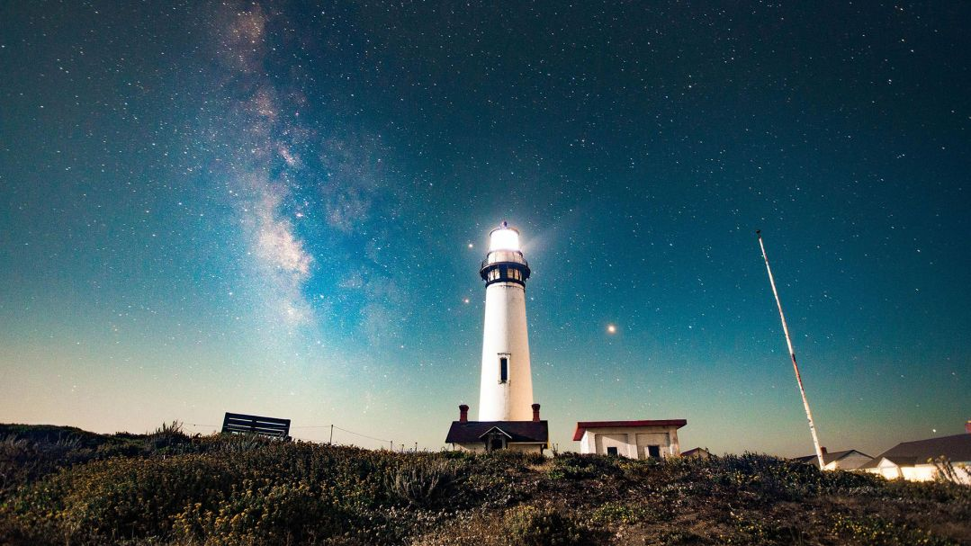 A white lighthouse lit up at night against a starry night background